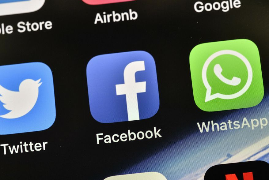 In this Nov. 15, 2018, file photo the icons of Facebook and WhatsApp are pictured on an iPhone in Gelsenkirchen, Germany. (AP Photo/Martin Meissner, File)