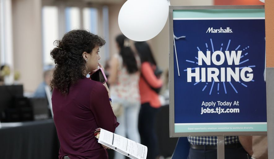 In this Oct. 1, 2019, file photo, Daisy Ronco waits in line to apply for a job with Marshalls during a job fair at Dolphin Mall in Miami. A new study released in late October found that 18-to-34-year-olds now have a 20% lower income level than Baby Boomers enjoyed when they were the same age in the 1980s. (AP Photo/Lynne Sladky, File) **FILE**