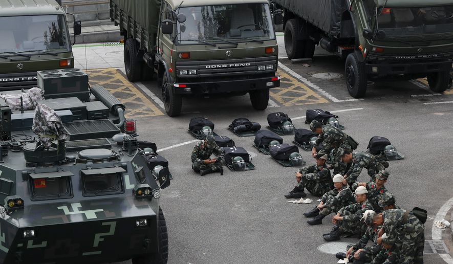 China has an estimated 12,000 PLA troops in Hong Kong, according to Reuters, and massed additional troops and military vehicles in nearby Shenzhen, where paramilitary police in riot gear are training. Beijing officials were notified in stark terms that any repeat of the use of military forces as in the 1989 Tiananmen Square massacre would spell the end of efforts to seek a resolution of the U.S.-Chinese trade war. (Associated Press/File)