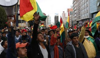 Coca leaf producers march against the reelection of President Evo Morales, in La Paz, Bolivia, Tuesday, Oct. 29, 2019. Morales' backers and foes are blocking streets and highways across the country in a dispute over official election results that show the leftist leader winning reelection without a runoff. (AP Photo/Juan Karita)