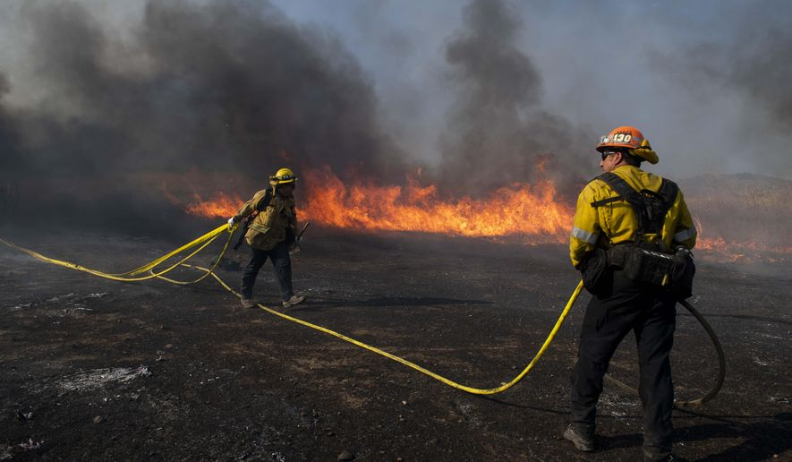 Firefighters work to prevent flames from reaching nearby homes while battling the Easy Fire, Wednesday, Oct. 30, 2019, in Simi Valley, Calif.  It has chewed through brush and trees near suburbs, horse ranches and the Ronald Reagan Presidential Library. (AP Photo/Christian Monterrosa)