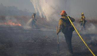 Firefighters work to prevent flames from reaching nearby homes as a helicopter drops water during the Easy Fire, Wednesday, Oct. 30, 2019, in Simi Valley, Calif. (AP Photo/Christian Monterrosa)