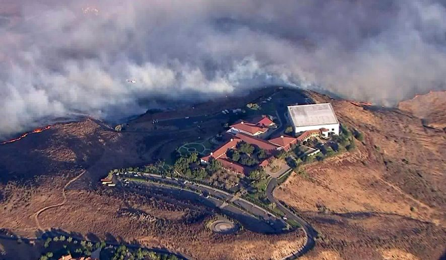 This photo from video provided by KTLA-TV shows the Ronald Reagan Presidential Library as flames from the Easy fire approach in Simi Valley, Calif., Wednesday, Oct. 30, 2019. The new wildfire erupted in wind-whipped Southern California, forcing the evacuation of the Library and nearby homes, as both ends of the state struggled with blazes, dangerously gusty weather and deliberate blackouts. Library spokeswoman Melissa Giller said the hilltop museum was safe  (KTLA-TV via AP)