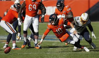 Chicago Bears quarterback Mitchell Trubisky (10) fumbles the ball in front of Los Angeles Chargers defensive end Damion Square (71) during the second half of an NFL football game, Sunday, Oct. 27, 2019, in Chicago. The Chargers won 17-16. (AP Photo/Charles Rex Arbogast)