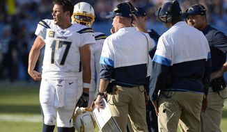 Los Angeles Chargers quarterback Philip Rivers (17) talks with coaches in the first half of an NFL football game against the Tennessee Titans Sunday, Oct. 20, 2019, in Nashville, Tenn. (AP Photo/Mark Zaleski)