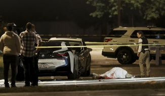 FILE - In this Aug. 20, 2017, file photo, a police detective walks past the body of a man fatally shot in the parking lot of an event center in Chicago. The Chicago Police Department must make significant changes in the way it investigates homicides in a city where more than half of killings go unsolved, a police research group said in a report released Wednesday Oct. 30, 2019. The Police Executive Research Forum found problems in the department that included inadequate training; a lack of a detective unit devoted solely to homicide investigations; and a failure to adequately help witnesses or even have a witness protection unit that is critical in persuading people to come forward to help solve crimes.(John J. Kim/Chicago Tribune via AP, File)