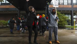 Chicago Teachers Union members, from left, Genevieve Roland (cq), a fifth year physics teacher and science department head, and Richie Foreman (cq), a second year counselor, stand on the picket line outside of Roberto Clemente Community Academy in Chicago on the tenth school day of the teachers strike, seen here on Wednesday, Oct. 30, 2019. CPS CTU (Jose M. Osorio/Chicago Tribune via AP)