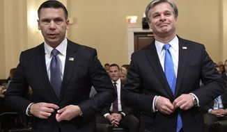 Acting Homeland Security Secretary Kevin McAleenan, left, and FBI Director Christopher Wray, right, prepare to testify before the House Homeland Security Committee on Capitol Hill in Washington, Wednesday, Oct. 30, 2019, during a hearing on domestic terrorism. (AP Photo/Susan Walsh)