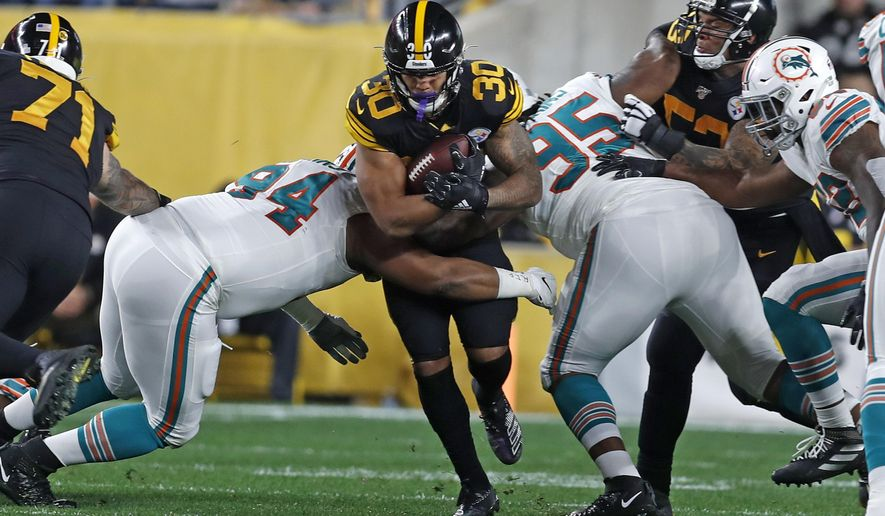 Pittsburgh Steelers running back James Conner (30) is tackled by Miami Dolphins defensive tackles Christian Wilkins (94) and John Jenkins (95) during the first half of an NFL football game in Pittsburgh, Monday, Oct. 28, 2019. (AP Photo/Keith Srakocic)