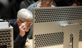 FILE - In this June 3, 2019, file photo Apple CEO Tim Cook, left, and chief design officer Jonathan Ive look at a Mac Pro in the display room at the Apple Worldwide Developers Conference in San Jose, Calif. Apple Inc. reports financial earns on Wednesday, Oct. 30. (AP Photo/Jeff Chiu, File)