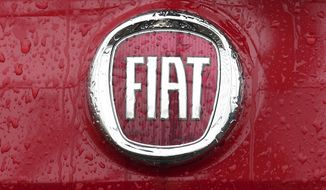 In this Jan. 2, 2014, file photo, a Fiat logo pictured on a car in Milan, Italy. Italian-American carmaker Fiat Chrysler Automobiles on Wednesday, Oct. 30, 2019, confirmed that it is in talks with French rival PSA Peugeot, its second bid this year to reshape the global auto industry facing huge challenges with the transition to electric and autonomous vehicles. (AP Photo/Antonio Calanni, File)