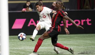 Toronto FC forward Tsubasa Endoh (31) takes a shot as Atlanta United defender Florentin Pogba (4) defends in the first half of their MLS Eastern Conference final soccer match Wednesday, Oct. 30, 2019 in Atlanta. (AP Photo/John Bazemore)