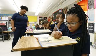 In this April 18, 2019 file photo, Elize'a Scott, a Key Elementary School third grade student, right, reads under the watchful eyes of teacher Crystal McKinnis, left in Jackson, Miss. Nationally, lower-performing students are doing worse in math and reading, thus dragging down overall results on the Nation's Report Card. Mississippi and the District of Columbia showed gains, along with some other big-city school districts. (AP Photo/Rogelio V. Solis, File) **FILE**