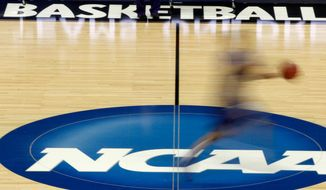 "In this March 14, 2012, file photo, a player runs across the NCAA logo during practice at the NCAA tournament college basketball in Pittsburgh. The NCAA Board of Governors took the first step Tuesday, Oct. 29, 2019, toward allowing athletes to cash in on their fame, voting unanimously to clear the way for the amateur athletes to ""benefit from the use of their name, image and likeness."" (AP Photo/Keith Srakocic, File) **FILE**"