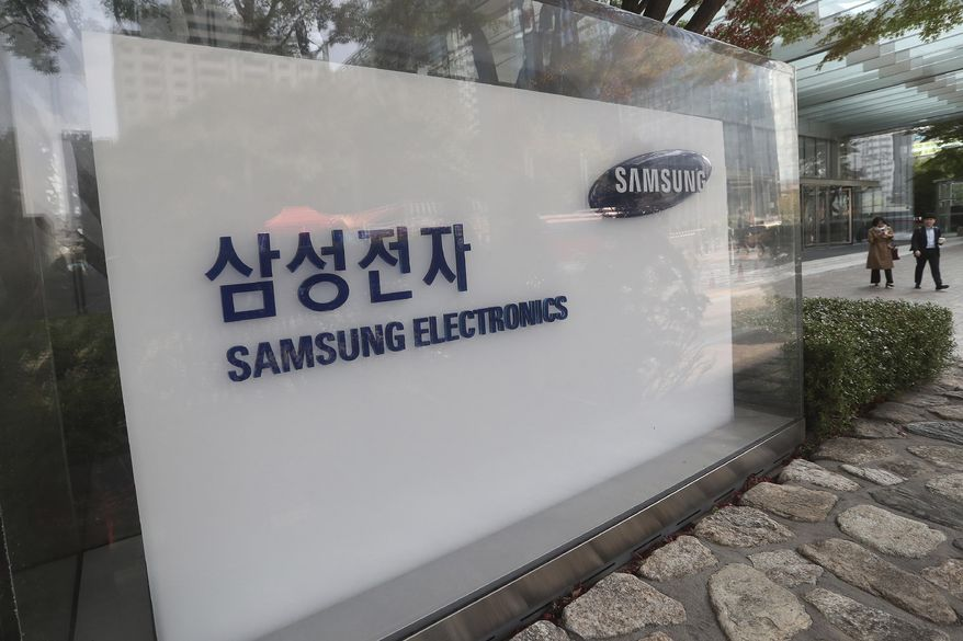 People walk near the logo of the Samsung Electronics Co. at its office in Seoul, South Korea, Thursday, Oct. 31, 2019. (AP Photo/Ahn Young-joon) ** FILE **