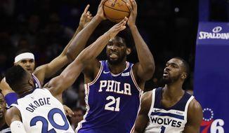 Minnesota Timberwolves' Josh Okogie (20) and Noah Vonleh (1) defend as Philadelphia 76ers' Joel Embiid (21) looks to pass the ball during the first half of an NBA basketball game Wednesday, Oct. 30, 2019, in Philadelphia. (AP Photo/Matt Rourke)