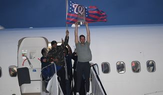 Washington Nationals manager Dave Martinez, left, waves a flag and Ryan Zimmerman, right, hoists the World Series trophy as the baseball team arrives at Dulles Airport, Thursday, Oct. 31, 2019, in Chantilly, Va. (AP Photo/Nick Wass)