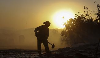 A firefighter puts out hotspots in Simi Valley, Calif., Wednesday, Oct. 30, 2019. (AP Photo/Ringo H.W. Chiu)