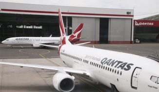FILE - In this Feb. 26, 2015, file photo, a Qantas 737 plane maneuvers behind another 737 parked at a gate at Sydney Airport in Sydney. Qantas on Wednesday, Oct. 31, 2019, said it had found cracking in one 737, following calls from the US Federal Aviation Administration for all airlines to check their fleets of the aircraft. (AP Photo/Rick Rycroft, File)