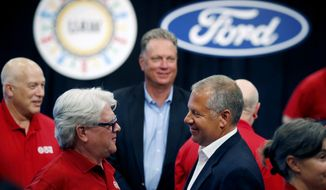 FILE - In this Monday, July 15, 2019, file photo, United Auto Workers Local 600 President Bernie Ricke, left, talks with Ford Motor Co., President Automotive Joseph R. Hinrichs after opening contract talks in Dearborn, Mich. The United Auto Workers union said late Wednesday, Oct. 30 that it has reached a tentative contract agreement with Ford after three days of intense bargaining. (AP Photo/Carlos Osorio, File)