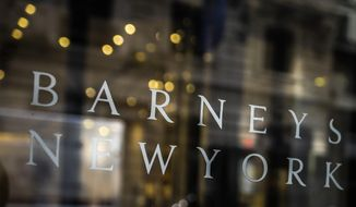 In this July 16, 2019, file photo signage for Barneys New York department store is displayed on the store's window in New York. Barneys New York says a bankruptcy judge has approved the sale of its assets to fashion licensing company Authentic Brands Group. (AP Photo/Bebeto Matthews, File) **FILE**