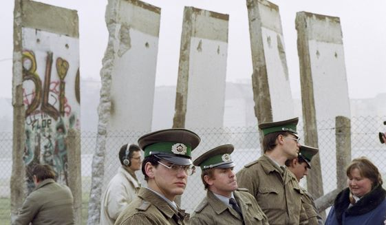 FILE - In this Monday, Nov. 13, 1989 file photo, East German border guards stand in front of segments of the Berlin Wall, which were removed to open the wall at Potsdamer Platz passage in Berlin. When the Berlin Wall fell, the Soviet Union stepped back, letting East Germany's communist government collapse and then quickly accepting German unification. (AP Photo/John Gaps III, File)
