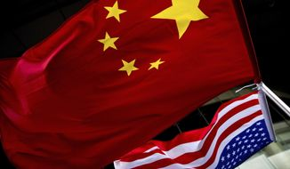 In this Nov. 7, 2012, photo, U.S. and Chinese national flags are hung outside a hotel during the U.S. Presidential election event, organized by the U.S. Embassy in Beijing. (AP Photo/Andy Wong) ** FILE **