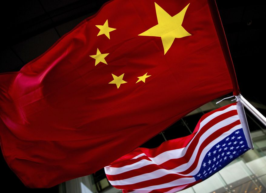 U.S. and Chinese national flags are hung outside a hotel during the U.S. Presidential election event, organized by the U.S. Embassy in Beijing. (AP Photo/Andy Wong)