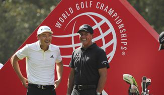 Li Haotong of China, left and Phil Mickelson of the United States chat before they tee off for the HSBC Champions golf tournament at the Sheshan International Golf Club in Shanghai on Thursday, Oct. 31, 2019. (AP Photo/Ng Han Guan)