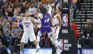 Utah Jazz guard Mike Conley (10) shoots as Los Angeles Clippers' Ivica Zubac (40) and Landry Shamet (20) defend during the first half of an NBA basketball game Wednesday, Oct. 30, 2019, in Salt Lake City. (AP Photo/Rick Bowmer)