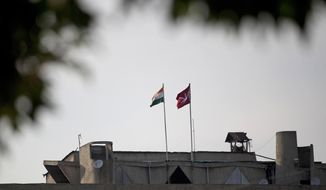 FILE - In this Aug. 9, 2019, file photo, an Indian national flag, left, flies next to a Jammu and Kashmir state flag on the government secretariat building in Srinagar, Indian controlled Kashmir. India on Thursday, Oct. 31, 2019 formally implemented legislation approved by its Parliament in early August that removes Indian-controlled Kashmir's semi-autonomous status and begins direct federal rule of the disputed area amid a harsh security lockdown and widespread public disenchantment. The most visible changes are the absence of Kashmir's own flag and constitution, which were eliminated as part of the region's new status. The Kashmiri flag, a symbol of its semi-autonomy, had always fluttered alongside India's national flag at the main government secretariat. (AP Photo/Dar Yasin, File)