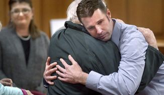 Erik Sackett embraces his father Ron Sackett after a not guilty verdict was announced Thursday, Oct. 31, 2019 at the La Crosse County Courthouse in La Crosse, Wis. A jury has acquitted Erik Sackett, a La Crosse man accused of killing his former girlfriend and disposing of her body in a lake.(Peter Thomson/La Crosse Tribune via AP)