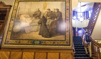 This Nov. 29, 2017, photo shows a murals of Christopher Columbus at Notre Dame in South Bend, Ind. The University of Notre Dame will cover murals in a campus building that depict Christopher Columbus in America, the school's president said, following criticism that the images depict Native Americans in stereotypical submissive poses before white European explorers. (Robert Franklin/South Bend Tribune via AP)