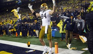 Notre Dame tight end Cole Kmet (84) receives debris thrown at him from the Michigan Stadium fans as he celebrates a touchdown in the third quarter of an NCAA college football game against Michigan in Ann Arbor, Mich., Saturday, Oct. 26, 2019. Michigan won 45-14. (AP Photo/Tony Ding)