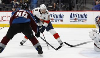 Florida Panthers center Jonathan Huberdeau, back left, scores the winning goal as Colorado Avalanche defenseman Samuel Girard, front left, and goaltender Philipp Grubauer defend in overtime of an NHL hockey game Wednesday, Oct. 30, 2019, in Denver. The Panthers won 4-3. (AP Photo/David Zalubowski)