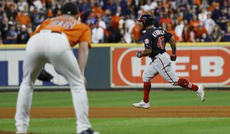 Houston Astros relief pitcher Will Harris watch as Washington Nationals' Howie Kendrick reacts after hitting a two-run home run during the seventh inning of Game 7 of the baseball World Series Wednesday, Oct. 30, 2019, in Houston. (AP Photo/Matt Slocum)
