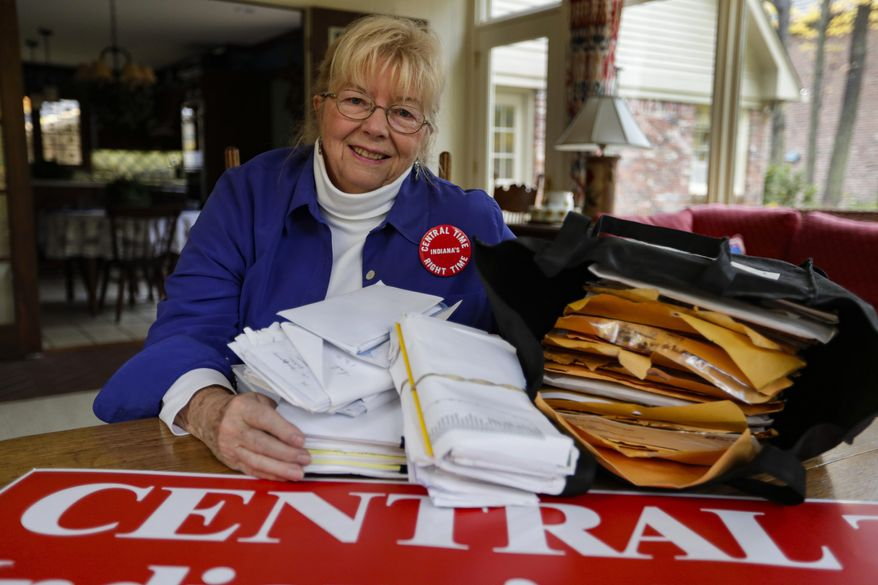 In this Thursday, Oct. 31, 2019, photo, Sue Dillon poses in her home in Carmel, Ind., with some of the petitions gathered to change Indiana time zone. Dillon became a campaigner for changes to the state's time choice after a teenager was fatally struck in 2009 while running to catch a school bus in the early morning darkness near her home. (AP Photo/Michael Conroy)