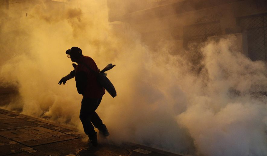 A protester against the reelection of President Evo Morales hurls a tear gas canister back at police during clashes in La Paz, Bolivia, Thursday, Oct. 31, 2019. Violence has escalated since Morales was declared the winner of the Oct. 20 vote amid delays in the vote count. The opposition alleges the outcome was rigged to give Morales enough of a majority to avoid a runoff election; the president denies any irregularities. (AP Photo/Juan Karita)