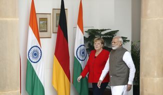Indian Prime Minister Narendra Modi, right, walks with German Chancellor Angela Merkel as they arrive for a delegation level meeting in New Delhi, India, Friday, Nov. 1, 2019. Merkel is on a three-day visit to India. (AP Photo/Manish Swarup)