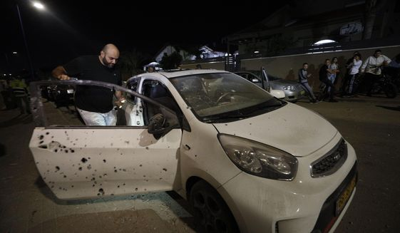 A man checks a car damaged iby shrapnel from a missile fired from Gaza Strip in Sderot, Israel, Friday, Nov. 1, 2019. Palestinian militants in Gaza fired barrages of rockets into southern Israel Friday, causing damage to a house and shattering nearly a month of calm across the volatile border. (AP Photo/Tsafrir Abayov)