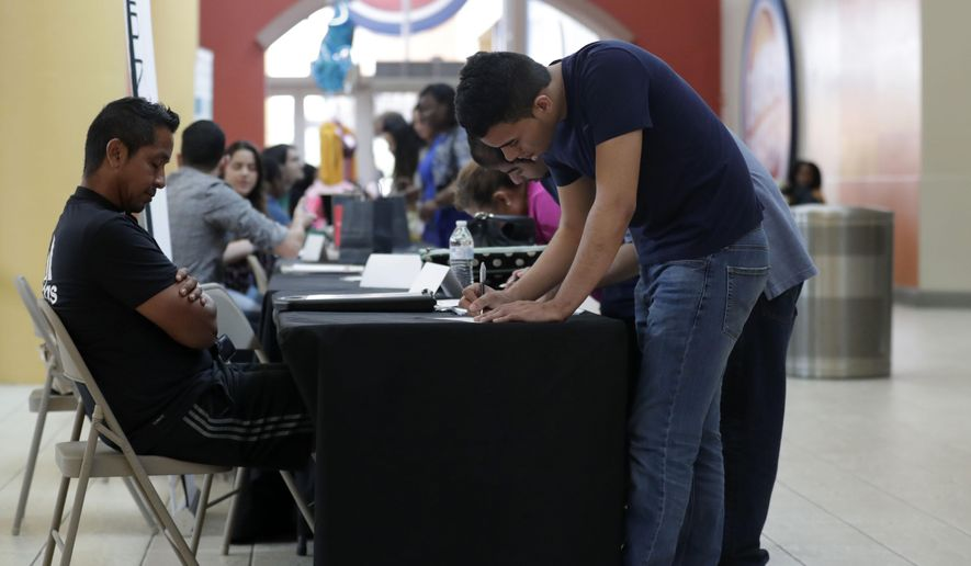 In this Oct. 1, 2019, file photo Billy Ramos, right, fills out a job application with Adidas during a job fair at Dolphin Mall in Miami. On Friday, Nov. 1, the U.S. government issues the October jobs report. (AP Photo/Lynne Sladky) ** FILE **