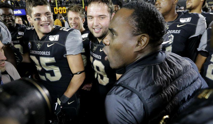 Vanderbilt head coach Derek Mason celebrates with his team, including Mitchell Pryor (25) and Scott Meyer (59), after Vanderbilt upset Missouri in an NCAA college football game Saturday, Oct. 19, 2019, in Nashville, Tenn. Vanderbilt won 21-14. (AP Photo/Mark Humphrey)