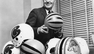 FILE - In this Jan. 3, 1968, file photo, Paul Brown, president of the New Cincinnati Bengals of the American Football League, is trying to select the design of helmets in Cincinnati, to be worn by his team when it starts play in the league. Brown, the innovative coach and powerful team owner who brought dozens of improvements to the sport, has been voted pro football's greatest game changer. (AP Photo/File)