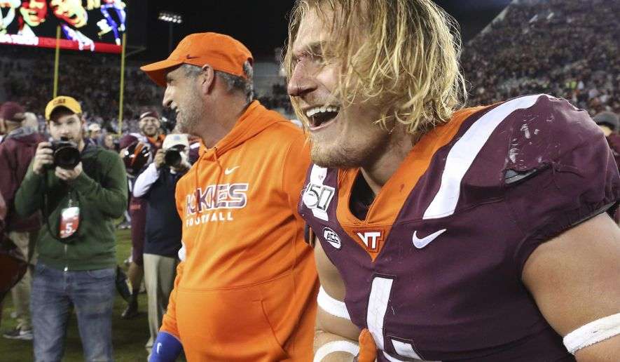 Virginia Tech defensive coordinator Bud Foster, front left, and linebacker Dax Hollifield (4) celebrate at the conclusion of an NCAA college football game  against North Carolina, Saturday, Oct. 19, 2019, in Blacksburg, Va. (Matt Gentry/The Roanoke Times via AP)