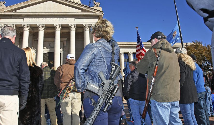 Leslie Nessmith, center, of Edmond, Okla., attends a rally at the state Capitol to mark the start of a new law that allows most adults in Oklahoma to carry a firearm in public without a background check or training, Friday, Nov. 1, 2019, in Oklahoma City. (AP Photo/Sue Ogrocki)