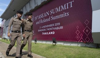 In this Tuesday, Oct. 29, 2019. Thai policemen walk in front of a banner welcoming Association of Southeast Asian Nations at the venue of The 35th annual Association of Southeast Asian Nations (ASEAN) in Nonthaburi province, Thailand. U.S. national security adviser Robert C. O'Brien and Commerce Secretary Wilbur Ross will represent President Donald Trump at two regional summits in Thailand this weekend, the White House announced, a move that would widely be viewed in the region as a snub. (AP Photo/Sakchai Lalit)