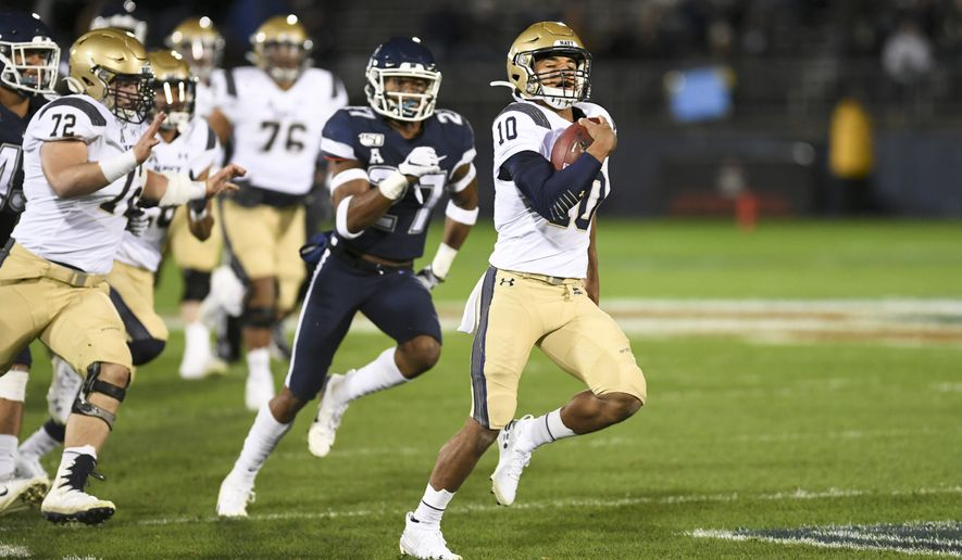 Navy quarterback Malcolm Perry (10) takes the ball in for Navy's first touchdown during the first half of an NCAA college football game against Connecticut on Friday, Nov. 1, 2019, in East Hartford, Conn. (AP Photo/Stephen Dunn) ** FILE **