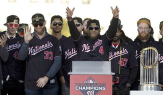 Washington Nationals head coach Dave Martinez accompanied by his players, speaks to the crowd during a rally following a parade to celebrate the team's World Series baseball championship over Houston Astros, Saturday, Nov. 2, 2019, in Washington. (AP Photo/Jose Luis Magana)