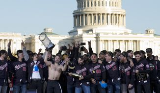 Washington Nationals player Brian Dozier with teammates, celebrates the World Series baseball championship during a rally following the parade to celebrate the team's World Series baseball championship over Houston Astros, Saturday, Nov. 2, 2019, in Washington. (AP Photo/Jose Luis Magana)