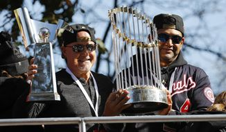 Washington Nationals general manager Mike Rizzo, left, and manager Dave Martinez hold up the NLCS trophy, left, and World Series trophy before a parade to celebrate the team's World Series baseball championship over the Houston Astros, Saturday, Nov. 2, 2019, in Washington. (AP Photo/Patrick Semansky)